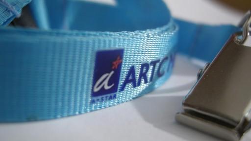 Närbild på nylonnyckelband med tryckt logotyp.