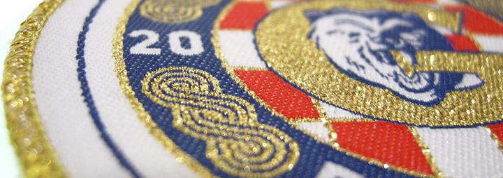 Vävt tygmärke med metallic tråd i guld.